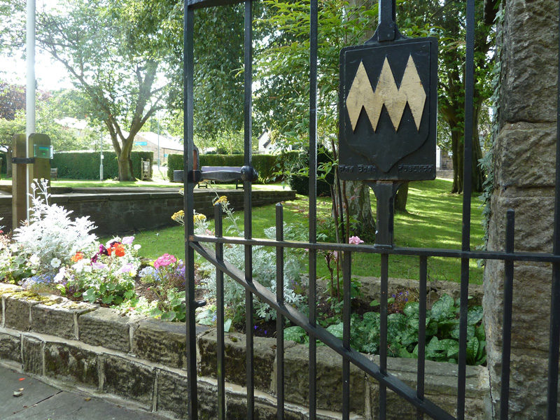 A gate into the park featuring the village shield